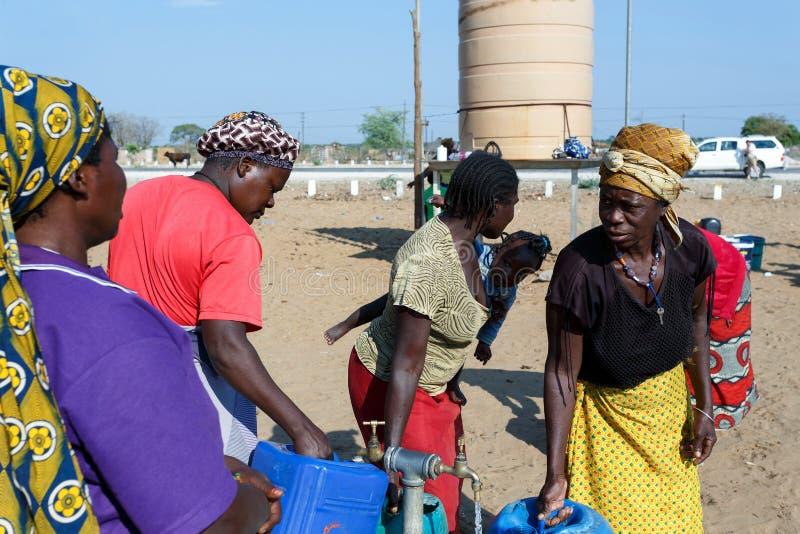 有孩子的未认出的纳米比亚妇女在与dri的公开坦克附近 库存照片