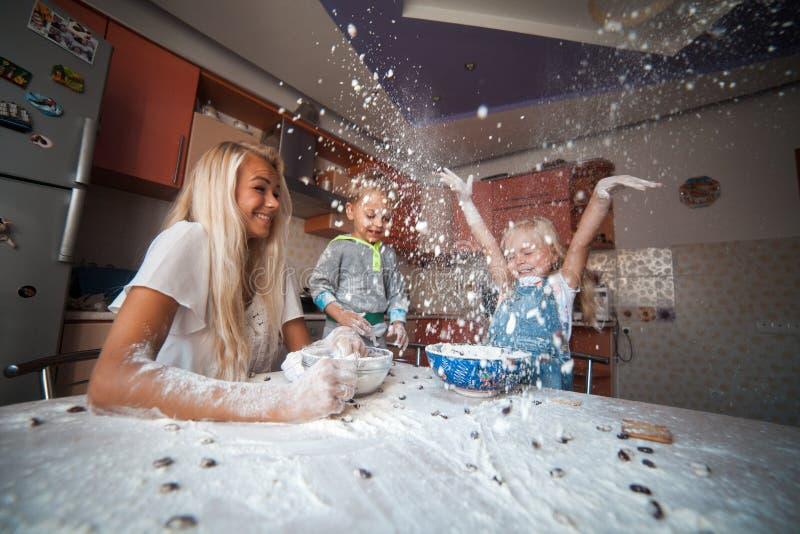 有孩子的母亲在上面的厨房投掷的面粉 库存照片