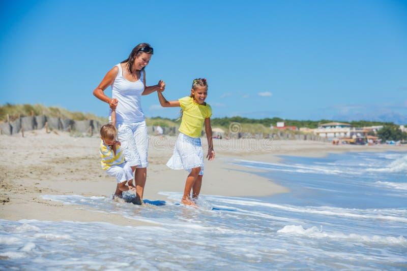 有孩子的母亲在海滩 库存图片