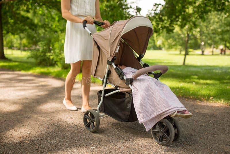 有孩子的母亲走在公园的婴儿推车的 库存照片