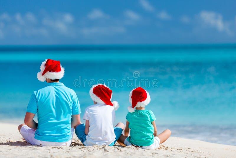 有孩子的父亲在圣诞节的海滩 免版税库存照片
