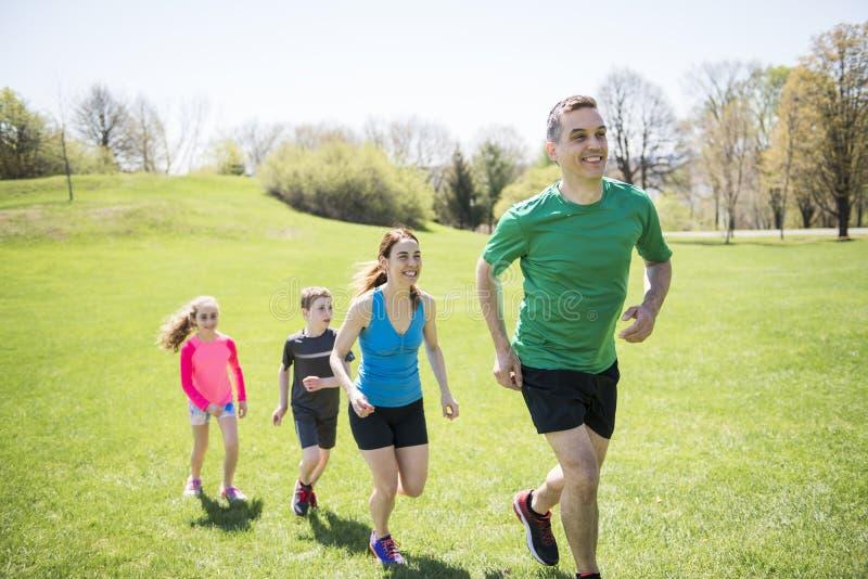 有孩子的父母炫耀一起跑外面 免版税库存图片
