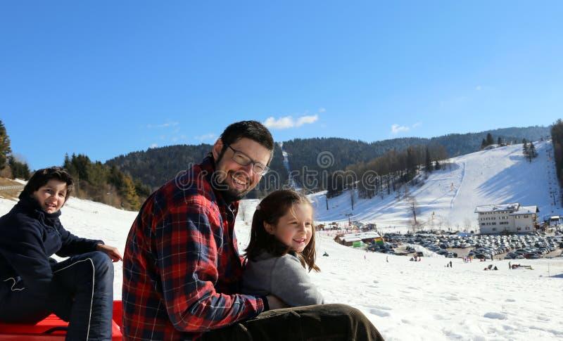 有孩子的爸爸sledding在白色雪的冬天 免版税库存照片
