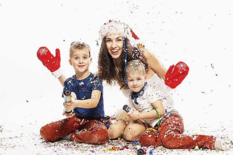 有孩子的美丽的年轻女人在五彩纸屑的圣诞节帽子的 图库摄影