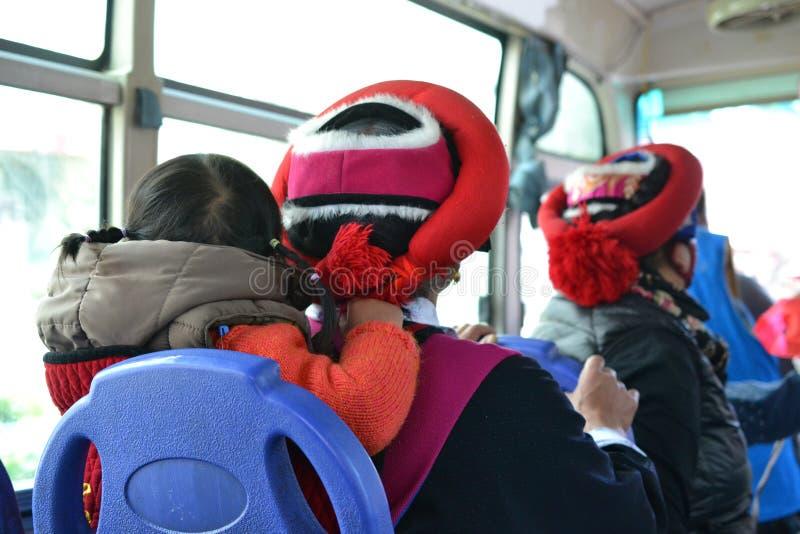 有孩子的西藏妇女从后面在一辆公共汽车上在Shangri La,Zhongdian,Xianggelila,云南-中国 免版税库存照片