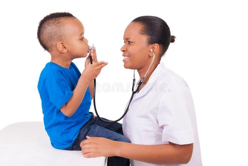 有孩子的非裔美国人的妇女医生 免版税图库摄影
