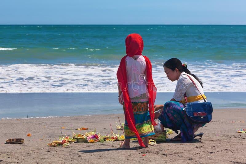 有孩子的巴厘语妇女海洋海滩的 免版税库存照片
