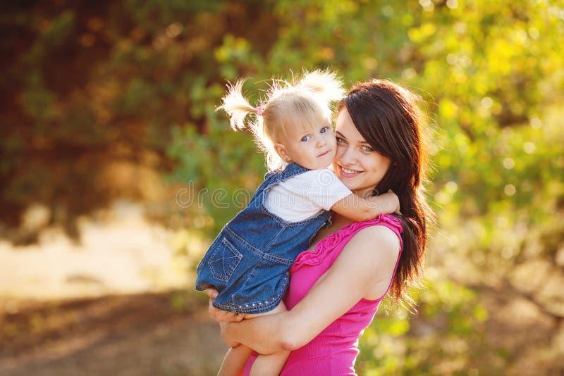 有孩子的年轻母亲外面在一个夏日 免版税库存照片