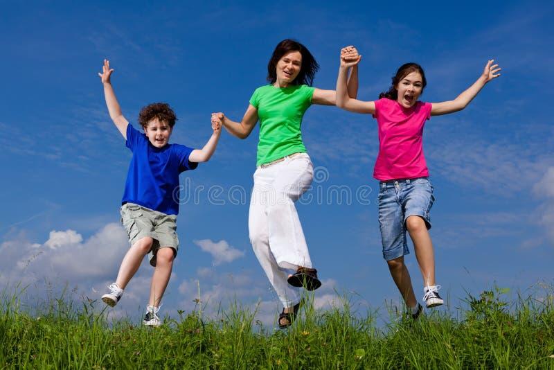 有孩子跳跃的母亲 库存照片