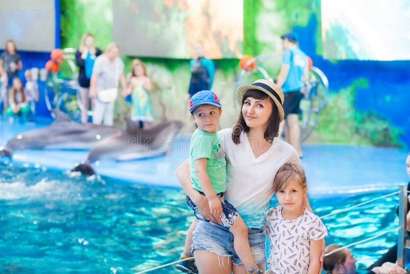有孩子dolphinarium的,shinochek在她的胳膊和女儿的母亲附近站立 库存照片