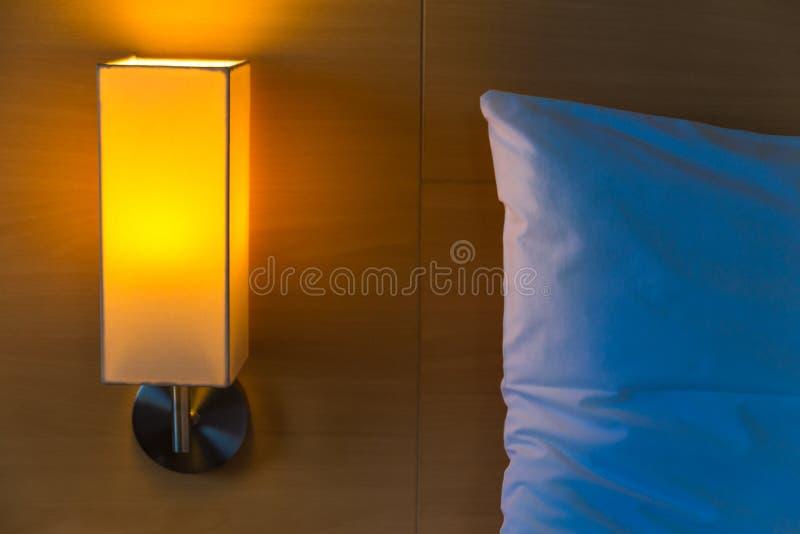 有它温暖的光的床头灯在白色床旁边打开了和 图库摄影
