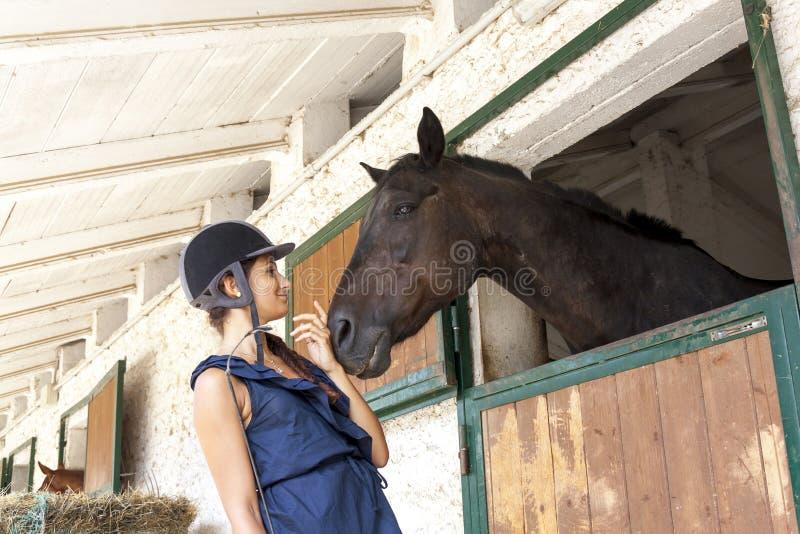 有它的马的年轻女骑士在槽枥 免版税库存照片