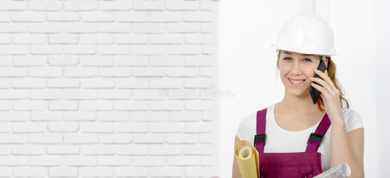有安全安全帽的年轻工程师妇女谈话在电话 库存照片