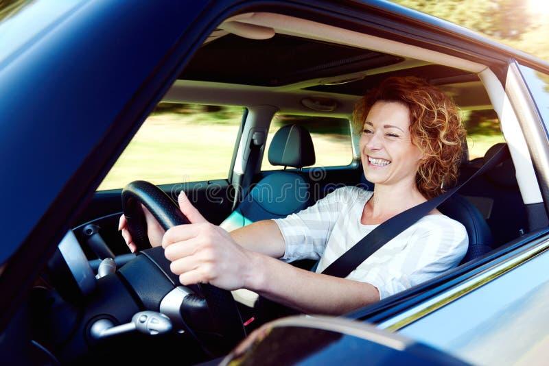 有安全带的愉快的女性司机指点汽车 免版税库存图片