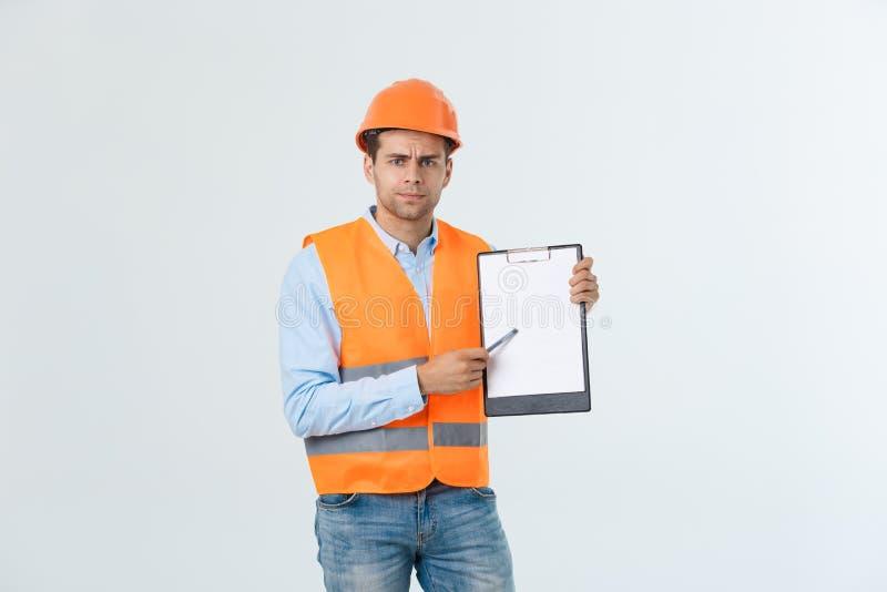 有安全帽和反射性背心的沮丧的年轻工程师检查在文件的差错的在灰色背景 库存照片