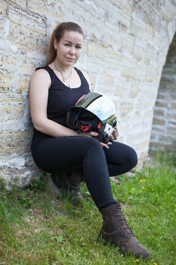 有安全帽在手中和防护起动的白种人妇女坐绿草 免版税库存图片