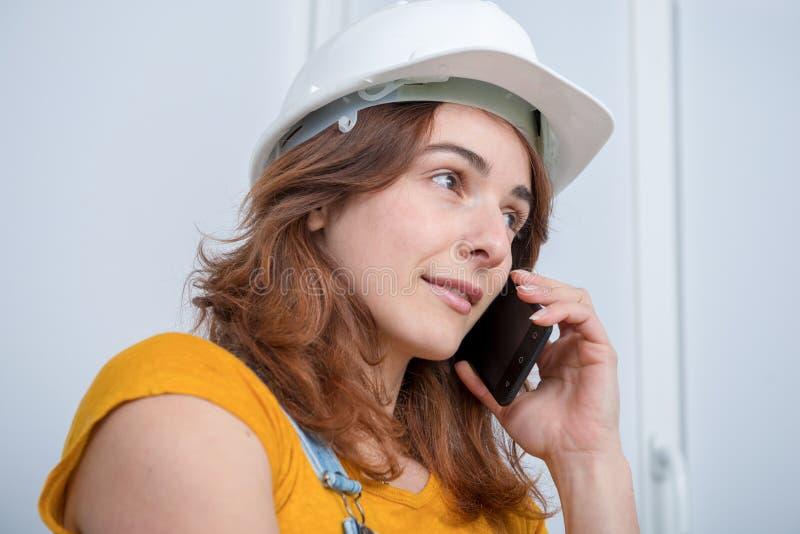 有安全帽的年轻工程师妇女谈话在电话 库存照片