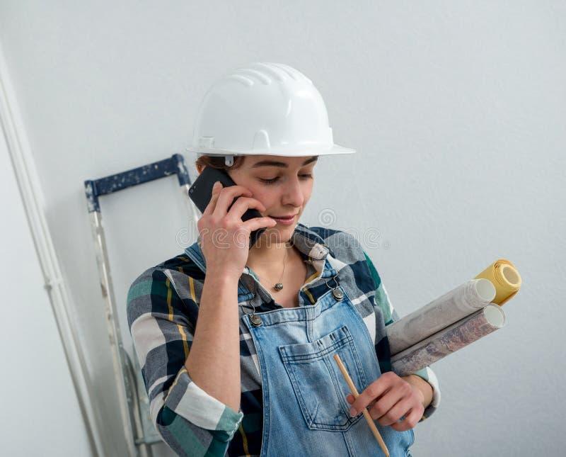 有安全帽的年轻工程师妇女谈话在电话 免版税库存照片