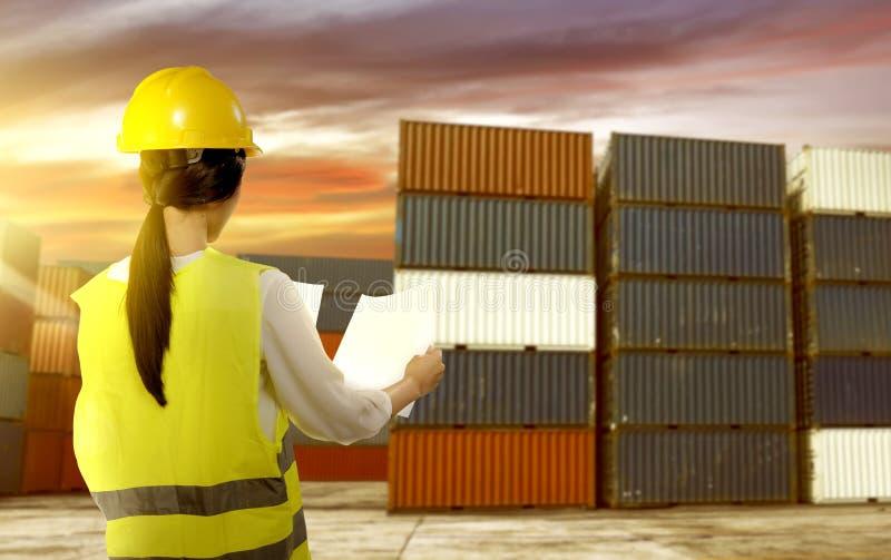 有安全背心和安全帽的拿着纸检查在船坞的亚裔女工背面图运输 免版税图库摄影