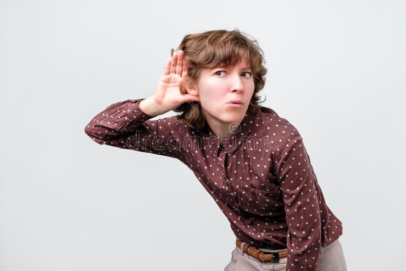 有安置手的卷发的妇女在她的耳朵,听殷勤地,设法偷听 库存图片