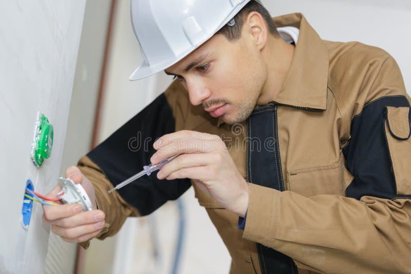 有安装壁上插座的螺丝刀的电工手 库存照片