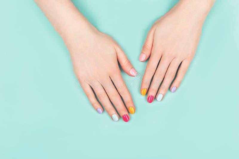 有完善的五颜六色的修指甲的妇女手 免版税图库摄影
