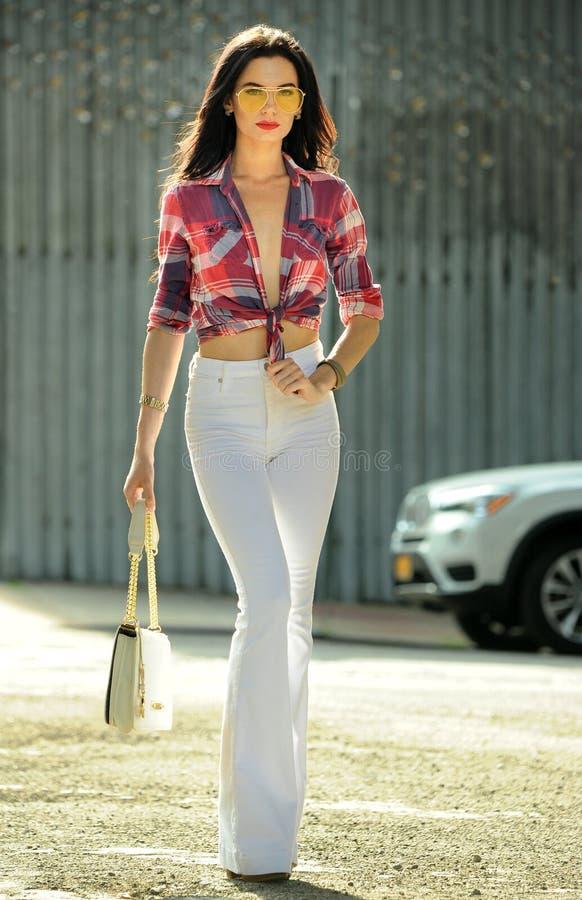 有完善的亭亭玉立的图的佩带的格子花呢上衣和白色裤子走时髦的深色的女孩在街道 库存照片