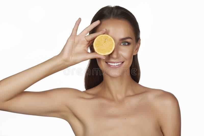 有完善的健康皮肤和拿着橙色柠檬葡萄柚的长的棕色头发天构成光秃的肩膀的美丽的性感的少妇 免版税库存照片