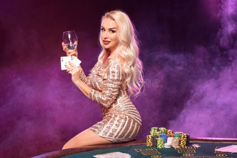 有完善的发型和明亮的构成的白肤金发的妇女在她的手上摆在与纸牌 赌博娱乐场,啤牌 免版税图库摄影