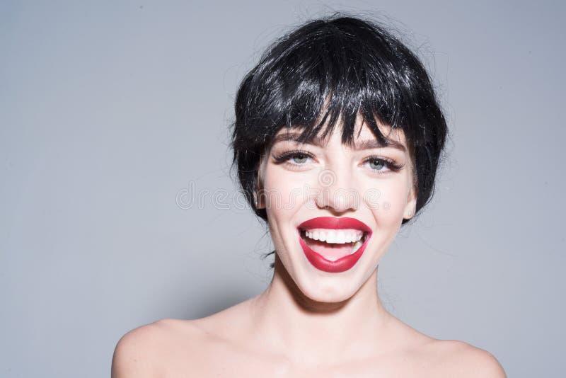 有完善的在灰色背景隔绝的微笑和红色嘴唇的快乐的小姐 花梢黑假发的笑的女孩  免版税库存图片