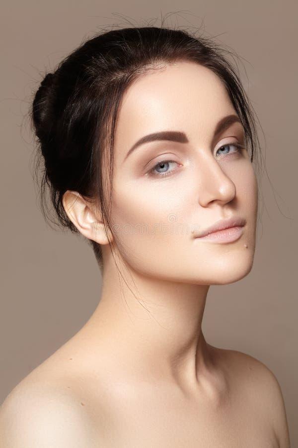 有完善的干净的发光的皮肤的,自然时尚构成美丽的少妇 模型魅力画象与逗人喜爱的小圆面包发型的 免版税图库摄影