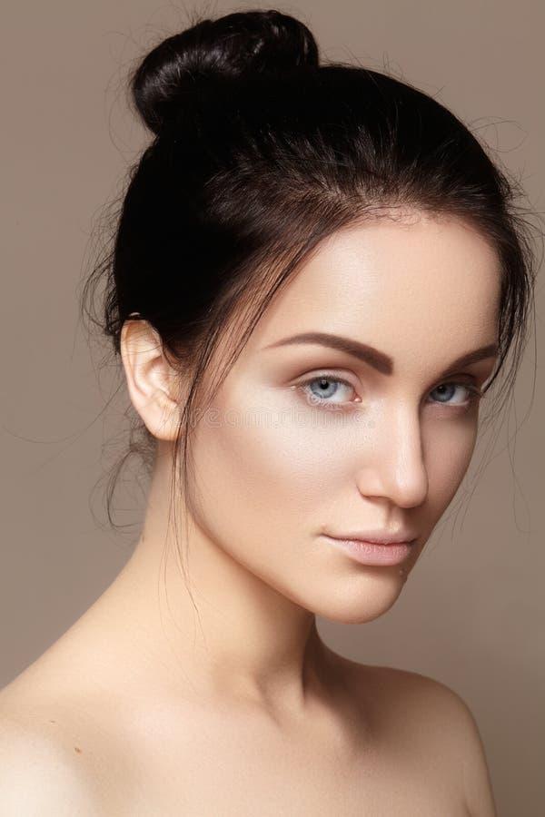 有完善的干净的发光的皮肤的,自然时尚构成美丽的少妇 模型魅力画象与逗人喜爱的小圆面包发型的 免版税库存图片
