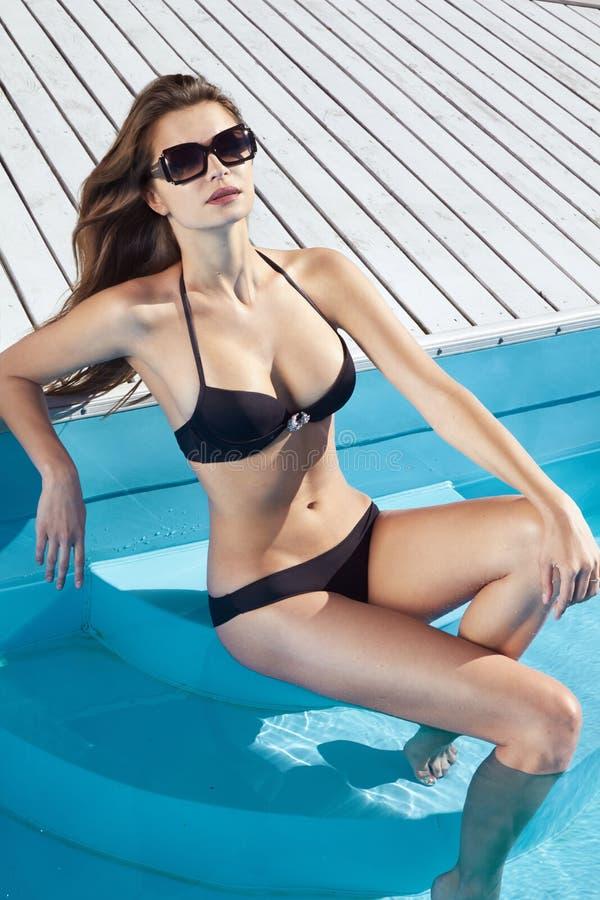 有完善的微小的图的美丽的性感的女孩与长的湿头发和游泳衣在时兴时髦太阳镜坐 免版税库存图片