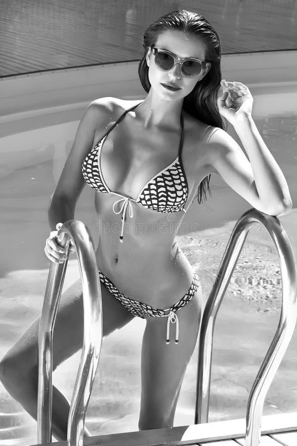 有完善的微小的图的美丽的性感的少妇与在时髦的玻璃的长的湿头发和游泳衣时尚从太阳来 免版税图库摄影