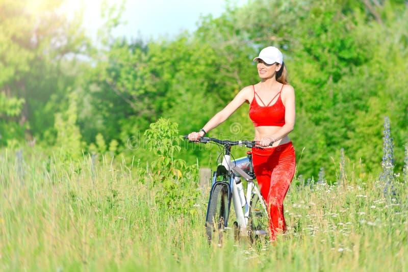 有完善的微笑的俏丽的妇女在公园草甸骑自行车 免版税库存图片