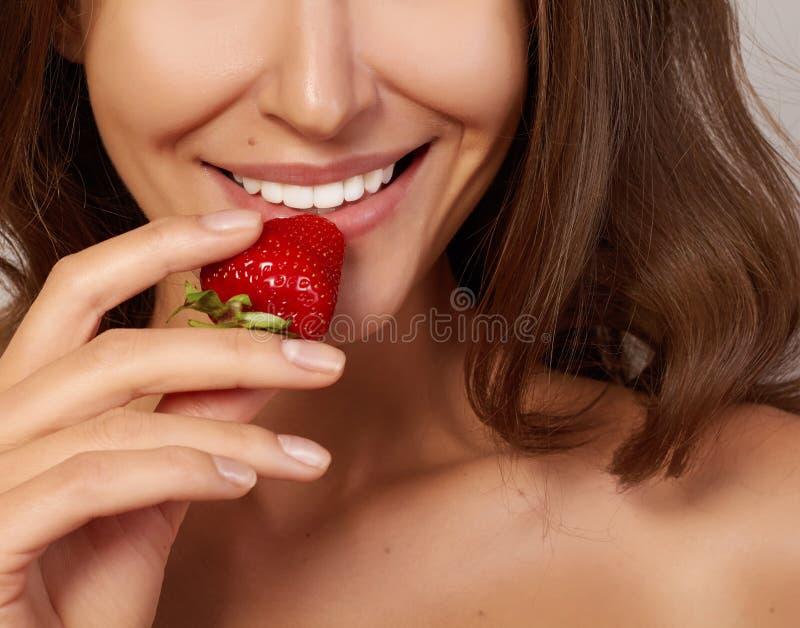 有完善的微笑的美丽的女孩吃红色草莓白色牙和健康食物 库存图片