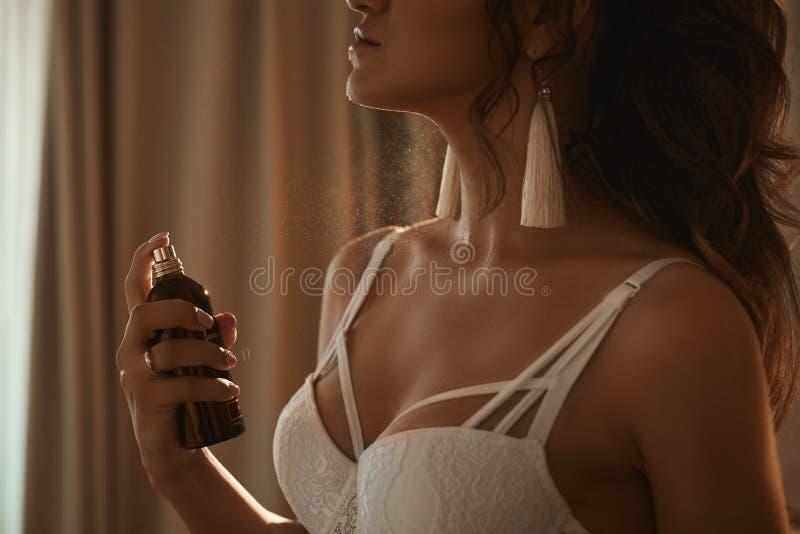 有完善的性感的身体的美丽和诱人的深色的式样女孩在应用在她的时兴的鞋带女用贴身内衣裤香水 免版税库存图片