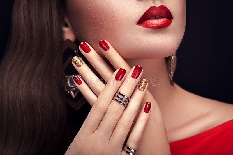 有完善的构成和红色和金黄修指甲佩带的首饰的美丽的妇女 免版税库存照片
