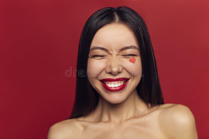 有完善的构成心脏的秀丽妇女在面孔 有吸引力的美好的时尚微笑的女孩爱构成情人节画象  免版税图库摄影