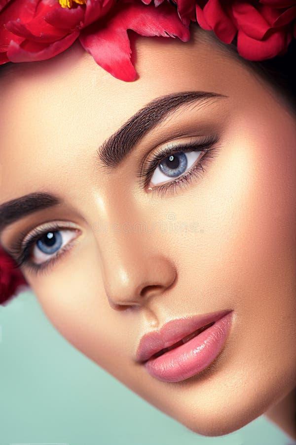 有完善的构成的秀丽女孩 应用光泽嘴唇组成专业人员 秀丽女孩在蓝色背景的` s面孔 免版税库存图片