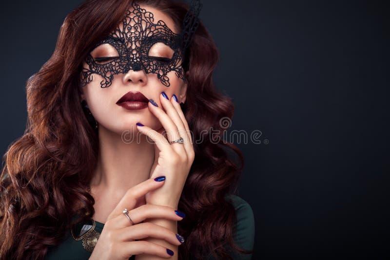 有完善的构成的美丽的戴着鞋带面具的妇女和修指甲 库存照片