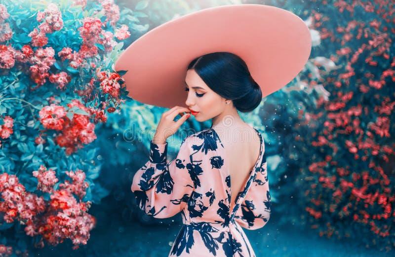 有完善的柔和的发型的逗人喜爱的妇女从戴桃红色帽子的长的黑色头发 库存图片