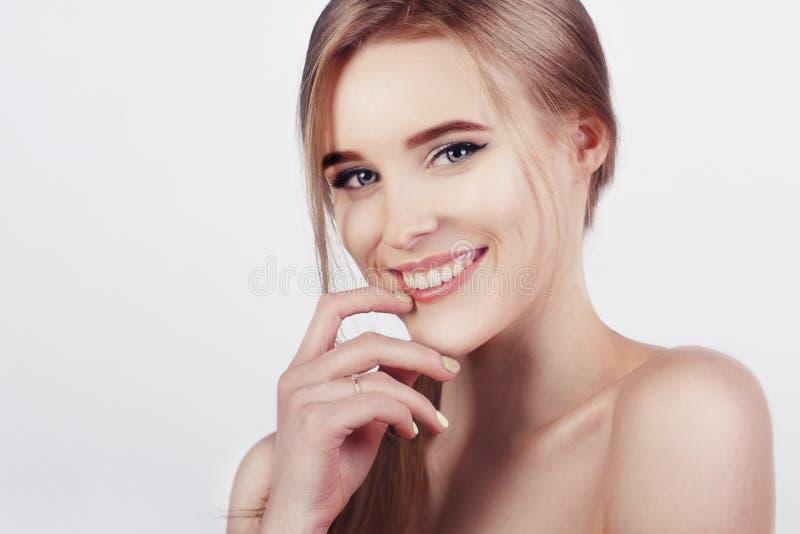 有完善的牙的愉快的快乐的少妇和干净的皮肤微笑 年轻新鲜的白肤金发的女孩美好的宽微笑  免版税库存照片