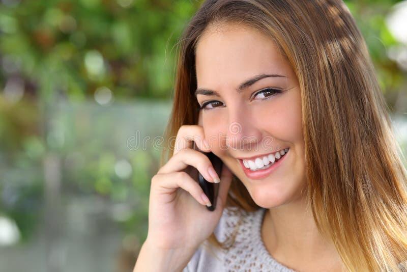 有完善的白色微笑的美丽的妇女谈话在手机 库存照片