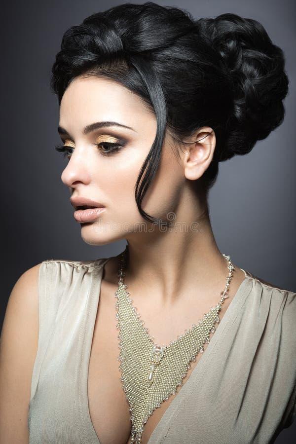 有完善的皮肤、金子构成和手工制造首饰的美丽的深色的妇女 秀丽表面 库存图片