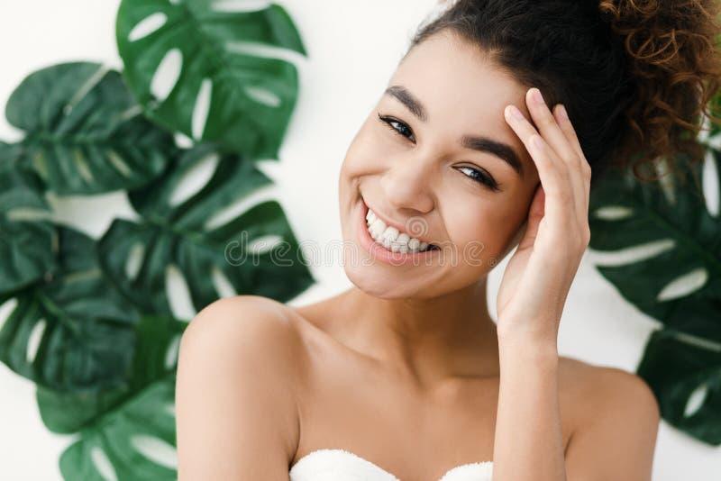 有完善的皮肤的非裔美国人的妇女在热带叶子 图库摄影