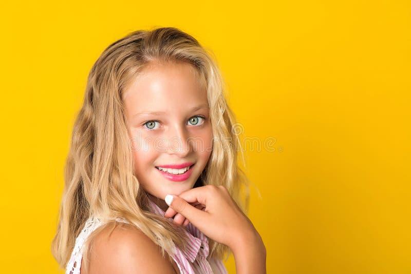 有完善的看对照相机的牙和微笑的坦率的青少年的女孩 美女面孔画象在黄色背景的12年 库存照片