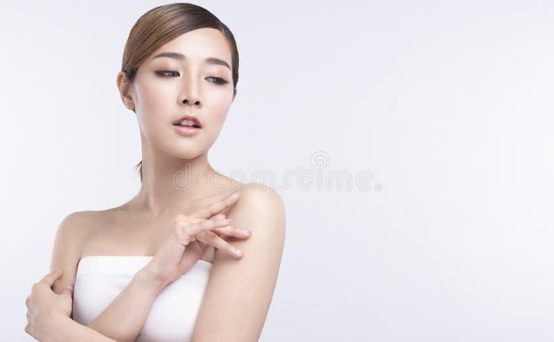有完善的脸皮的秀丽年轻亚裔妇女 广告治疗温泉和整容术的姿态 免版税库存照片