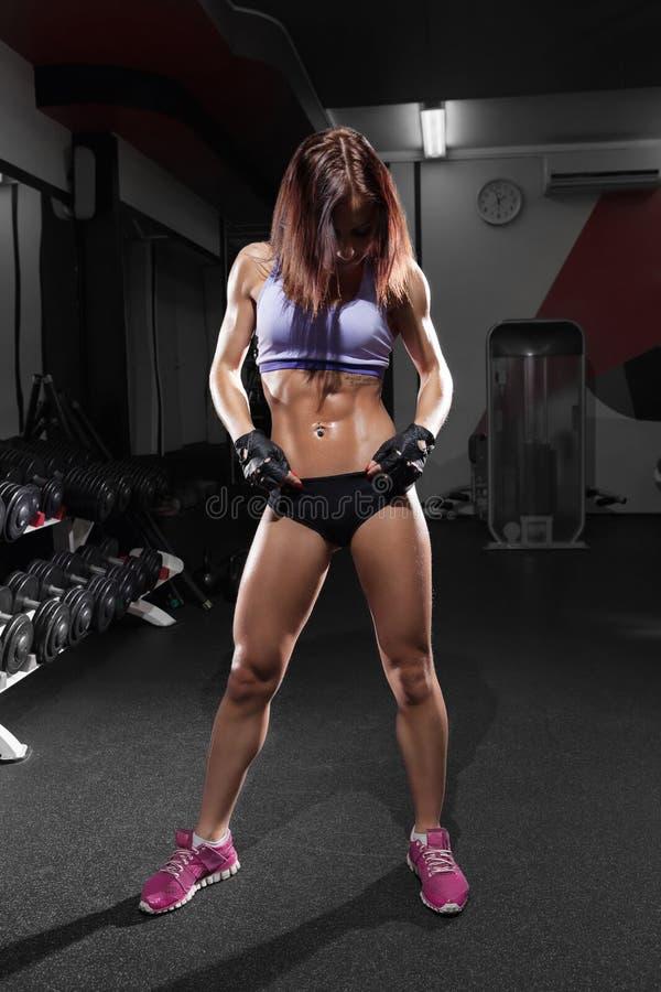 有完善的腹肌的美丽的性感的女孩在健身房 一健康生活方式和锻炼的