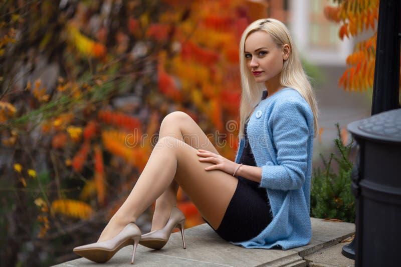 有完善的腿和蓝色女衬衫摆在的美丽的白肤金发的女孩室外在秋天公园的街道上设置光的  免版税图库摄影